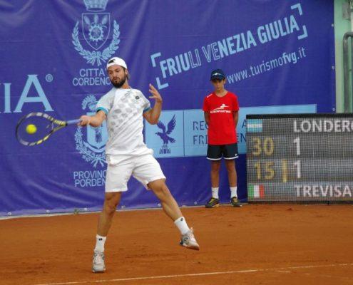 Tennisspieler vor einer Tennisblende